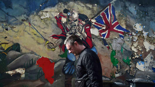 A man walks past a mural marking unionist territory on May 4, 2016 in Londonderry, Northern Ireland.