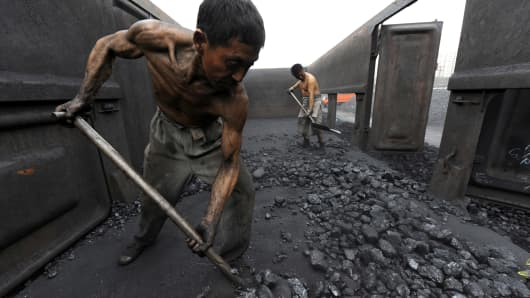 Workers unload coal at a storage site along a railway station in Hefei, Anhui province.