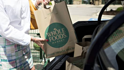 A customer loads shopping bags into a vehicle outside a Whole Foods Market Inc. location in Naperville, Illinois, U.S., on Friday, June 16, 2017.