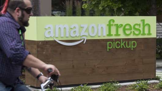 A man rides a bicycle near an AmazonFresh Pickup location on June 16, 2017 in Seattle, Washington.