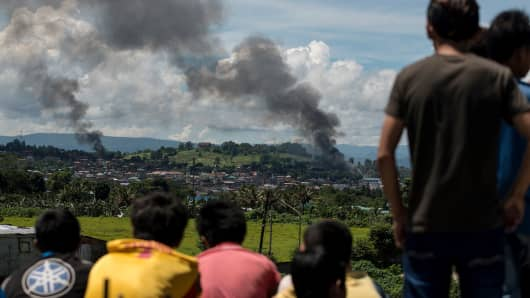 People watch as smoke billows from houses after aerial bombings by Philippine Airforce planes on Islamist militant positions in Marawi on the southern island of Mindanao on June 17, 2017. Philippine troops have been pounding militants holding parts of Marawi City with air strikes and artillery. The death toll has risen to more than 300 after nearly a month of fighting.