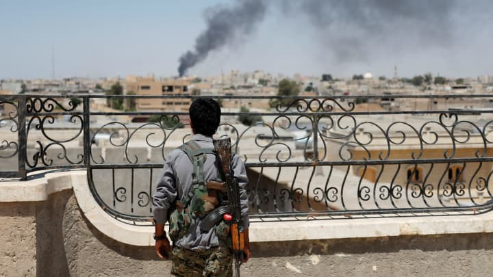 A Kurdish fighter from the People's Protection Units (YPG) looks at a smoke after an coalition airstrike in Raqqa, Syria June 16, 2017.