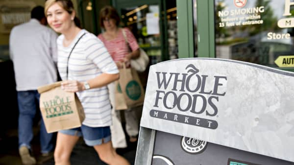 Shoppers exit a Whole Foods Market location in Naperville, Ill.