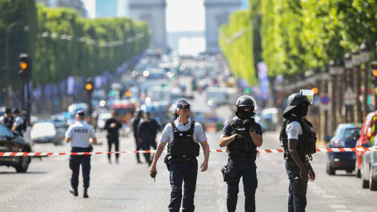 Police officers and anti-riot police officers patrol the Champs-Elysees avenue on June 19, 2017 on the Champs-Elysees avenue in Paris.