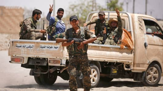 Syrian Democratic Forces (SDF) fighters carry their weapons in Raqqa's western neighbourhood of Jazra, Syria June 11, 2017.