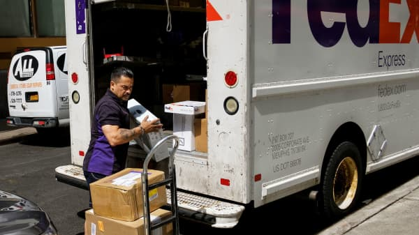 A FedEx delivery driver unloads packages from his truck in Lower Manhattan, June 2, 2017 in New York City.