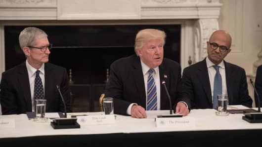 US President Donald Trump speaks next to Microsoft CEO Satya Nadella (R) and Apple CEO Tim Cook (L) during an American Technology Council roundtable at the White House