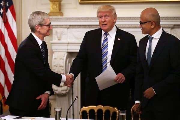 U.S. President Donald Trump (C) greets Apple CEO Tim Cook (L) and Microsoft CEO Satya Nadella before a meeting of the American Technology Council in the State Dining Room of the White House