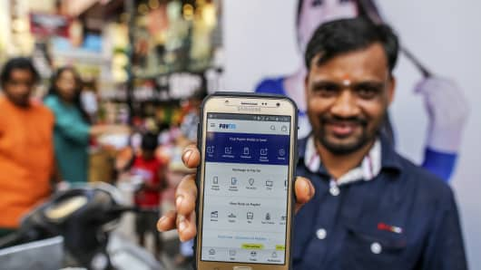 The Paytm mobile digital payment app displayed here helps financial inclusion in India, as does M-Pesa in Kenya but more such initiatives are needed says a new report from Village Capital and the Bill and Melinda Gates Foundation.