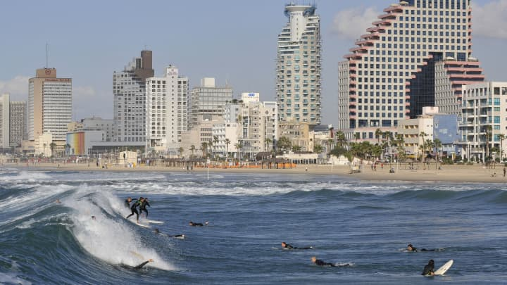 Surfers ride the waves on a beach in Tel Aviv, Israel