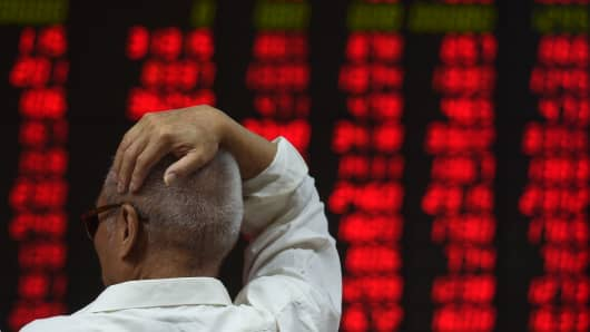 An investor watches stock price movements at a securities company in Beijing.