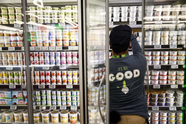 A Whole Foods employee stocks yogurt.