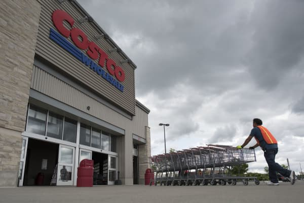 An employee pushes a row of shopping carts into a Costco Wholesale Corp. store in East Peoria, Illinois, U.S.