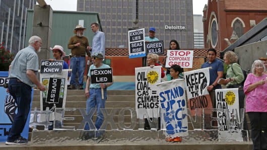 People protest across Morton H. Meyerson Symphony Center where the Exxon Mobil annual shareholder meeting is taking place, in Dallas.
