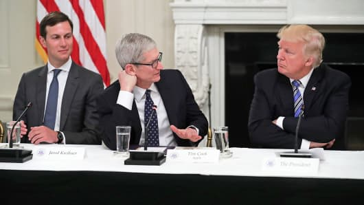 Apple CEO Tim Cook delivers brief remarks as U.S. President Donald Trump (R) and White House Director of the Office of American Innovation and the president's son-in-law Jared Kushner listen during a meeting of the American Technology Council in the State Dining Room of the White House June 19, 2017 in Washington, DC.