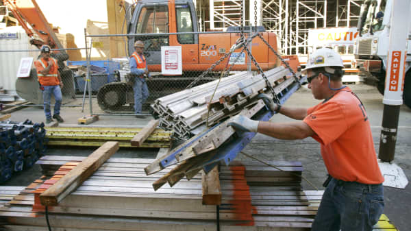 Construction workers move materials at a work site for a new condominium and retail complex in Portland, Oregon.