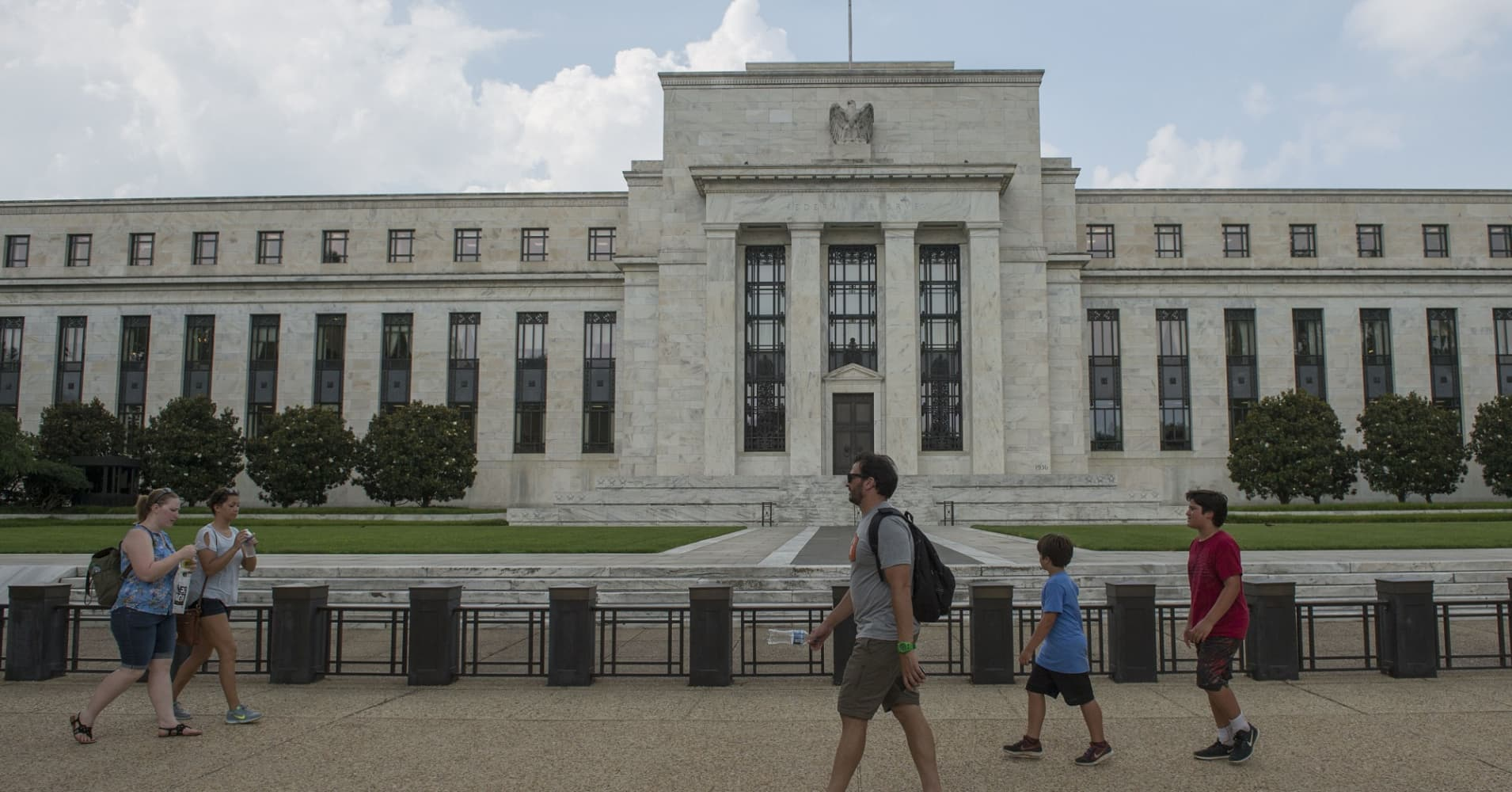Tourists walk in front of the Federal Reserve in Washington, D.C.