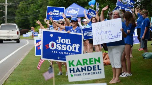 Supporters for Georgia 6th Congressional District Democratic candidate Jon Ossoff rally and wave at passing cars outside St Mary's Orthodox Church, Handel's polling place in Roswell.