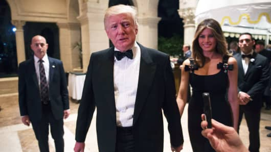 Then-President-elect Donald Trump answers questions from reporters, accompanied by his wife, Melania, on New Year's Eve, December 31, 2016, at Mar-a-Lago in Palm Beach, Florida.