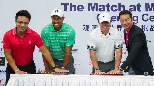 Tiger Woods (2nd from left) of the United States and Rory McIlroy (2nd from right) of Northern Ireland with Ken Chu (l), Chairman and CEO of Mission Hills Group, and Tenniel Chu (r), Vice Chairman of Mission Hills Group, attend the opening ceremony of 'The Match at Mission Hills', the golf duel between Tiger Woods and Rory McIlroy, at the Blackstone Course.