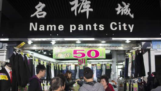 People browse a clothing store in Shangxiajiu Pedestrian Street in Guangzhou, China, on November 29, 2013.
