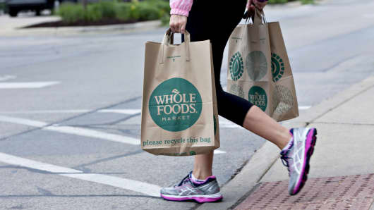 A customer carrying shopping bags exits a Whole Foods Market Inc. location in Naperville, Illinois, on June 16, 2017.