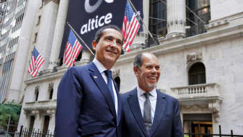 Altice founder Patrick Drahi, left, and co-founder Armando Pereira pose for photos outside the New York Stock Exchange, before the company's IPO, Thursday, June 22, 2017.