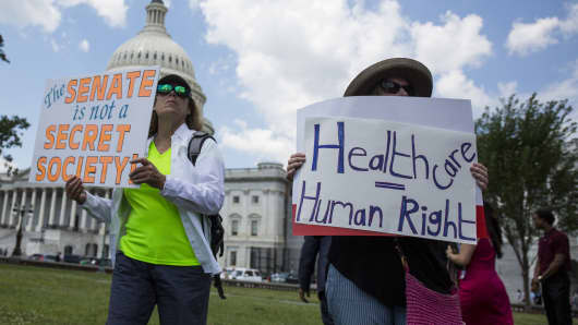 Demonstrators hold signs during a healthcare rally opposing the American Health Care Act (AHCA) bill on Capitol Hill in Washington, D.C., U.S., on Wednesday, June 21, 2017.