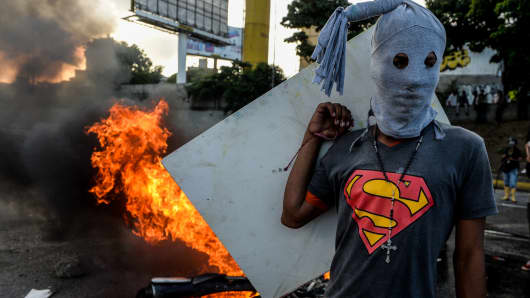 A ​​hooded demonstrator stands near a burning motorbike in clashes with the riot police during an anti-government protest in Caracas, on June 22, 2017.