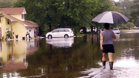 In this image taken from video, Erin West walks down a flooded street in her neighborhood after Tropical Storm Cindy, Thursday, June 22, 2017, in Ocean Springs, Miss.