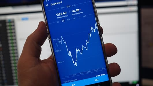 A phone showing an ethereum price chart on the Coinbase exchange platform.