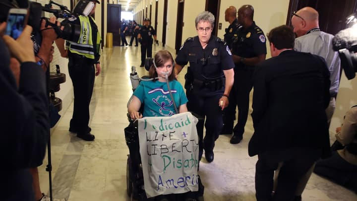 U.S. Capitol Police remove a protester from in front of the office of Senate Majority Leader Mitch McConnell (R-KY) inside the Russell Senate Office Building on Capitol Hill, on June 22, 2017 in Washington, DC.