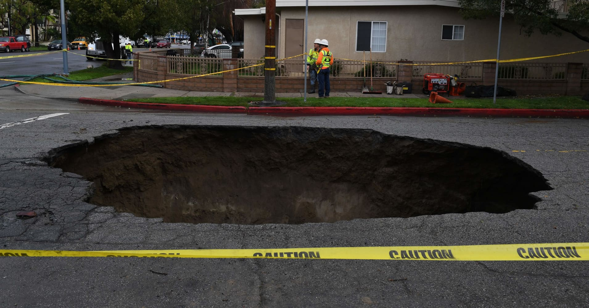 A large 20-foot-deep (6-meter) sinkhole that swallowed two vehicles in North Laurel Canyon Blvd, in Los Angeles, is cordoned-off on February 18, 2017, after a powerful storm hit southern California.