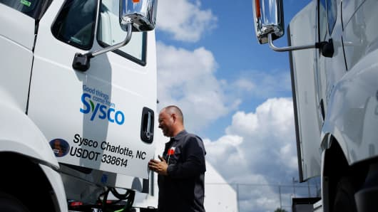 A worker exits the cab of a delivery truck outside of the Sysco distribution center in Concord, North Carolina.