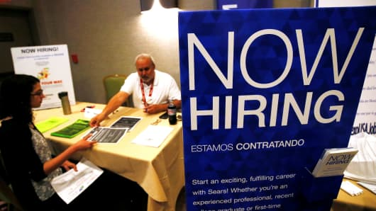 A job applicant (L) talks with a recruiter for Sears at a job fair in Golden, Colorado.