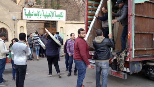 Egyptian Coptic Christians unload their belongings from a truck as they arrive to take refuge at the Evangelical Church in the Suez Canal city of Ismailiya on February 24, 2017.