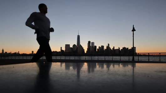 A man jogs past the skyline of lower Manhattan at sunrise in New York City.