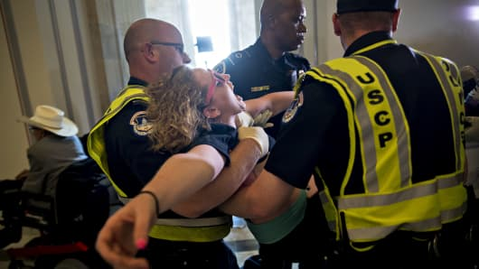 A demonstrator protesting cuts to Medicaid is carried away from the office of Senate Majority Leader Mitch McConnell by U.S. Capitol police officers at the Russell Senate Office building in Washington, D.C., U.S., on Thursday, June 22, 2