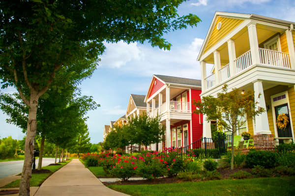 Row of colorful garden homes with two stories and white pillars in suburban neighborhood of Fayetteville, Arkansas.