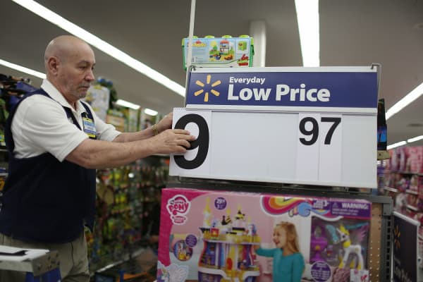 An employee puts a low price dollar sign together at a Walmart store.