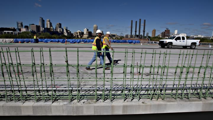 Workers walk on the I-35W St. Anthony Falls Bridge over the Mississippi River in Minneapolis, Minnesota.