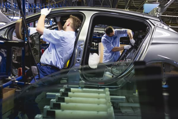 Workers assemble an Opel Astra automobile near a supply of glass panels at the Opel automobile plant in Gliwice, Poland, on Monday, March 6, 2017.