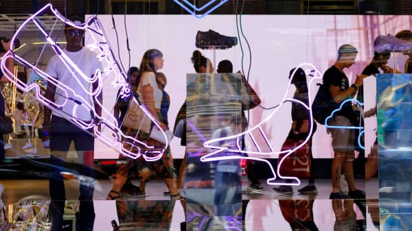 Seen through the store window, shoppers browse in a Nike store in New York City.