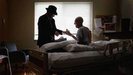 Terminally ill patient Jim Staloch (R), caresses a dove on October 7, 2009 while at the Hospice of Saint John in Lakewood, Colorado.