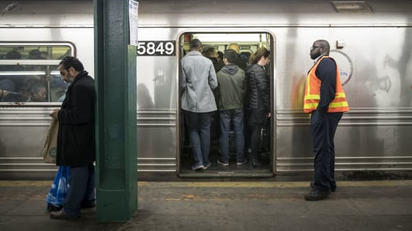 An MTA worker looks on as people stand on an idling train.