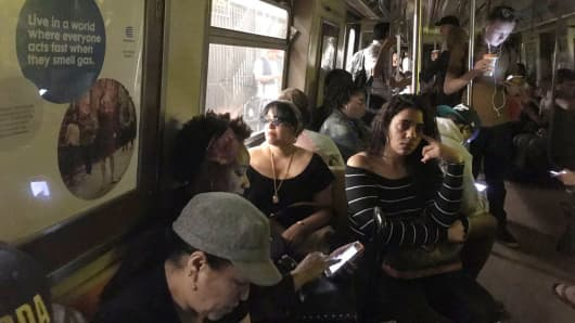 Passengers wait on a halted with a power outage on an MTA train at 125th station on June 27th 2017