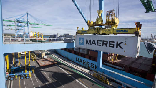 A crane loads a shipping container branded A.P. Moller-Maersk onto a freight ship.