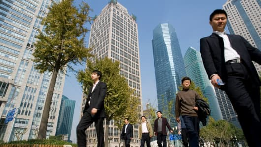 Employees walk in Luziajui business district of Shanghai, China.