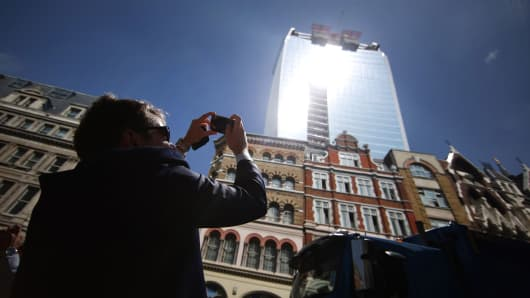 """A man takes a photograph as the sun glares down from the """"Walkie-Talkie"""" office building in the financial district on September 4, 2013 in London."""