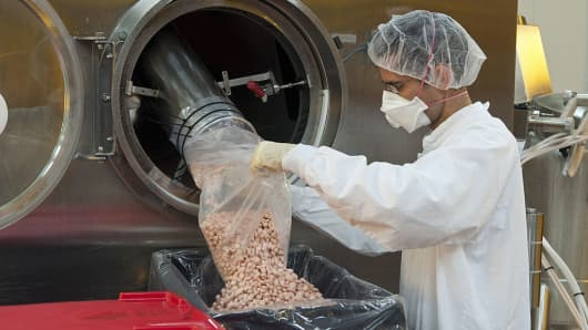 An employee collects newly-manufactured pills at the tablet production plant at Teva Pharmaceutical Industries Ltd.'s headquarters in Jerusalem, Israel.